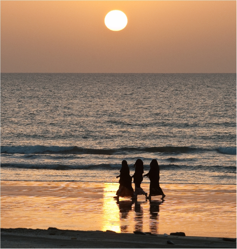 Three women walk along the sand and admire a stunning sunset